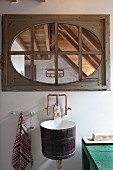 Sink made from wooden tub mounted on wall below lattice window with wooden frame