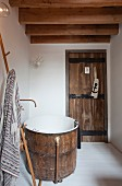Rustic wooden tub and wooden door with wrought iron fittings in small bathroom