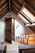 Rustikales Zimmer mit sichtbarem Dachstuhl, schlichter Armlehnstuhl unter Dachfenster
