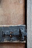 Wrought iron door latch on rustic wooden door