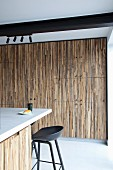 Kitchen counter and black bar stool in front of fitted cupboards with slatted wooden fronts below black steel girder on ceiling