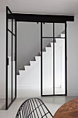White masonry staircase with integrated storage in minimalist stairwell seen through glass and steel doors