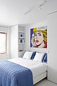 Double bed with blue bedspread below Pop-Art picture by Roy Lichtenstein in white modern bedroom