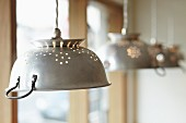 Four metal colanders used as lampshades for pendant lamps