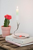 Lit candle on candlestick made from bent vintage fork stuck to saucer with washi tape in ront of flowering cactus