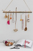 Kitchen utensils hung on suspended wooden rod with hooks above open cookery book, scissors and wire basket