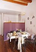 Gedeckter Tisch vor Theke mit violetten Paneelen, seitlich an Wand Deko Buchstaben