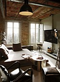 Living-sleeping area with armchair and stool next to bed and flatscreen TV on wall in rustic interior with brick wall and ceiling