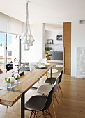 Bundle of lamps above simple, designer wooden table and Eames Plastic Chairs; sliding door leading to kitchen in background