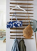 Bags, jackets and a hanger on a homemade coat rack made from driftwood