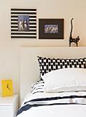 Schwarzweisser Mustermix auf Kissenbezügen, dekorativen Bilderrahmen und Deko-Katze über dem Bett