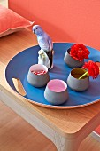 A set of bowls and a porcelain budgerigar on a cornflower blue tray against a coral-coloured wall