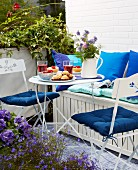 Gedeckter Tisch auf sonnigem Balkon mit leichten platzsparende Klappmöbeln und Truhenbank