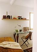 Gelbe, gemusterte Tagesdecke auf Bett, seitlich Klappstuhl und postmoderner Tisch, darüber Wandboard