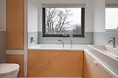 Bathroom with custom wooden elements and bathtub below window