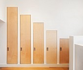 Custom fitted cupboards with stepped wooden door elements in hallway