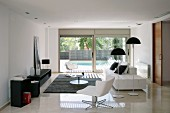 Modern living room in black and white; white swivel chair and standard lamps with mushroom-shaped lampshades next to contemporary sofa