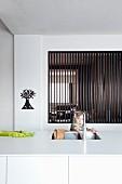 Kind hinter weisser Kücheninsel mit Spülbecken, im Hintergrund Durchreiche mit dunklen Holzlamellen