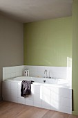 Fitted bathtub with white-tiled front in niche with green-painted walls