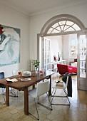 Holztisch und moderne Stühle mit Sitzschalen vor offener Flügeltür, oberhalb halbkreisförmiges Oberlicht, Blick auf rote Liege im Wohnzimmer
