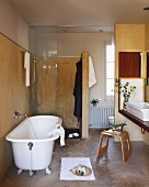 Free-standing, vintage bathtub in front of floor-level shower with glass door and wooden stool in front of washstand in renovated bathroom