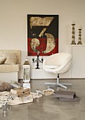 Collection of objects on polished concrete floor in front of retro swivel chair, modern printed artwork and candlesticks on shelves