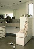 L-shaped concrete washstand with base cabinet, half-height partition with tip-on drawers and integrated stool