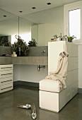 Beton-Waschtisch, übereck mit Spiegelfront und Unterbauschrank; seitlich ein halbhoher Raumteiler mit Tipp-On-Schubladen und Ablage-Hocker