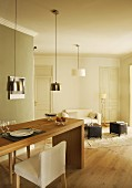 Dining table made from solid wooden panels, upholstered chairs and modern pendant lamps with metal lampshades in open-plan interior