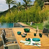 View from wooden deck with outdoor dining area to adjacent pool; vegetation and palm trees in background