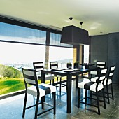 Black and white designer dining area next to continuous glass wall with view of landscape