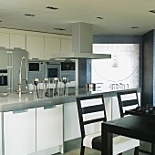 Counter with sink and cooker in modern, open-plan, fitted kitchen; dining area with black and white stripe chairs in foreground