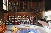 Zweigeschossiger Loftraum mit Bücher- und Schreibtischfront unter offener Kleidergalerie; mittig ein großer Teppich mit Schaukeln und Holzpferd
