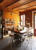 Bar stools with copper seats and mobile breakfast bar in loft-apartment kitchen with brick ceiling; open-fronted metal shelving against wall