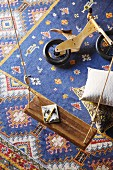 View down onto child's balance bike and simple swing above blue Oriental rug