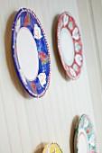 Vier dekorative Teller mit rotem, blauem, grünem und gelbem Rand an weisser Holzwand
