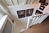 Blick von oben auf historische Bilder im Abgang einer gewendelten Landhaustreppe