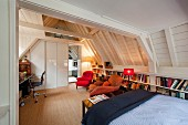 Multifunctional attic room with home office, seating area, bookcases and bed under exposed, white-painted wooden roof structure