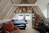 Narrow, multifunctional attic room with TV chair, fitted shelving at knee wall height and double bed