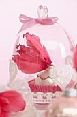Christbaumkugel dekoriert mit pinkfarbenen Alpenveilchenblütenblättern unter Glasglocke