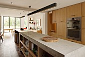 Long concrete kitchen counter below rod-shaped pendant lamps opposite fitted cupboards with wooden fronts
