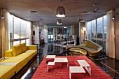Filigrane Couchtische aus weiss lackiertem Metall, auf rotem Teppich, Polstercouch in Gelb und goldenes Sofa von Zaha Hadid
