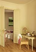 Rattanstuhl vor zierlichem Wandtisch mit Schnitzereien, neben offener Flügeltür und Blick ins Wohnzimmer