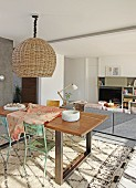 Pendant lamp with wicker lampshade above dining set with vintage chairs and patterned rug in front of lounge area in modern interior