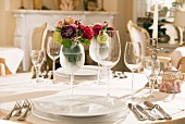 Festively set table with place settings, wine glasses and posy in wine glass labelled with name