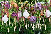 White lanterns and flowers hanging from washing line in garden