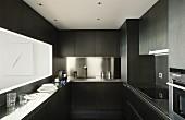 Dark designer kitchen with stainless steel splashback and hatch above narrow counter
