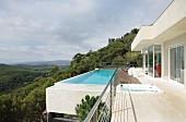Weitblick in bewaldete Landschaft vom umlaufenden Balkon und Infinity-Pool eines modernen Ferienhauses