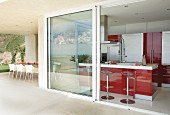 Designer bar stools at island counter with red fronts seen through open sliding doors leading from terrace of modern holiday home