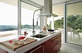 Blick von Küchenblock mit roten Schubladenfronten durch umlaufende Fensterfronten auf teilweise überdachte Terrasse